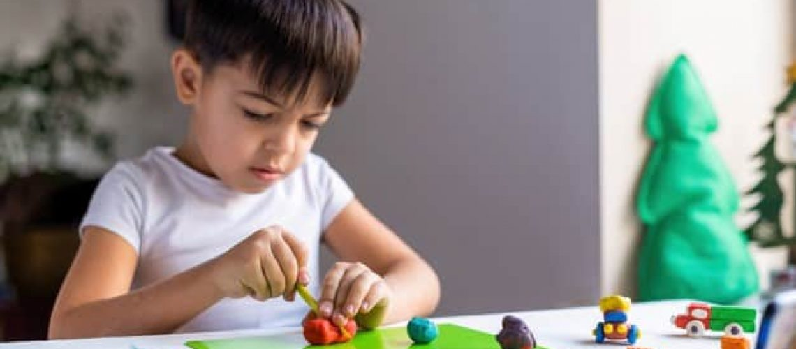 small-caucasian-boy-playing-with-colored-plasticine-making-figures-white-table-happy-child-idea_1268-16984